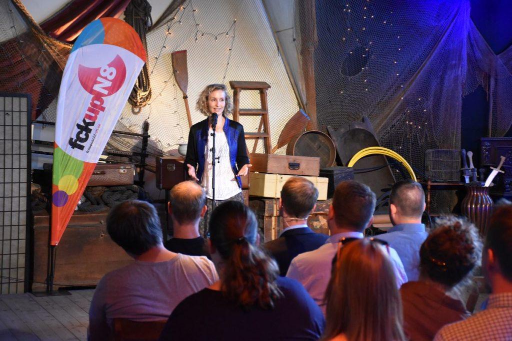 Bühnenfoto von Monika Mertens am Mikrofon bei einer Fuckup Night vor Publikum.