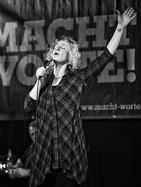 Bühnenfoto von Monika Mertens in schwarz-weiß bei einem Poetry Slam, performt leidenschaftlich mit starken Gesten auf der Bühne.