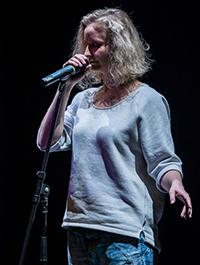 Bühnenfoto von Monika Mertens bei einem Poetry Slam, performt mit geschlossenen Augen am Mikrofon.